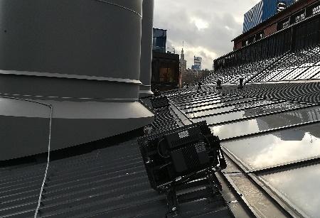 Montaż   reflektora na dachu budynku.